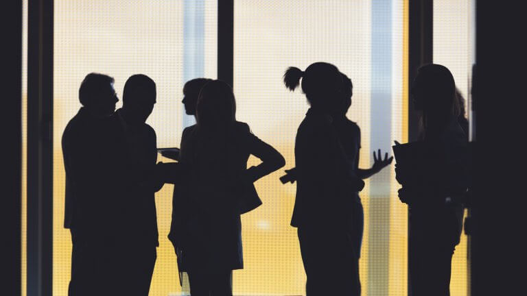 Silhouettes of a group of business people standing in the office building