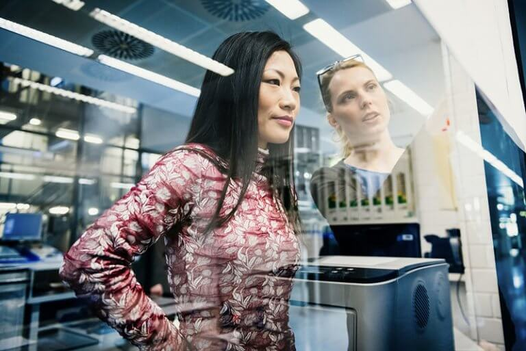 Two businesswomen discussing a project office while looking at documents pinned on a glass wall